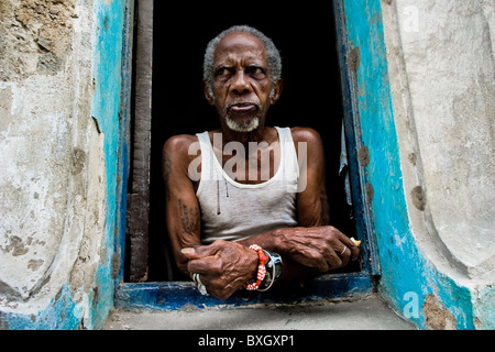 A Cuban man, the Palo Monte priest, wearing a typical red and white bracelet, looks out of the window in Havana, - Stock Photo