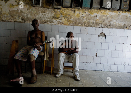 Cuban men, the Afro-Cuban religion belivers, sitting in a passage of the old house in Havana, Cuba. - Stock Photo
