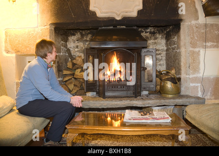 Woman sitting on a sofa in front of a roaring log fire keeping warm - Stock Photo