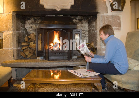 Woman sitting on a sofa in front of a roaring log fire reading a newspaper - Stock Photo