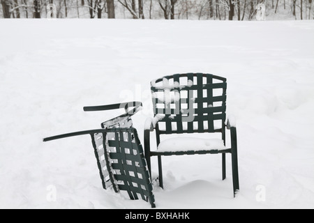 Two outdoor chairs covered in snow. - Stock Photo