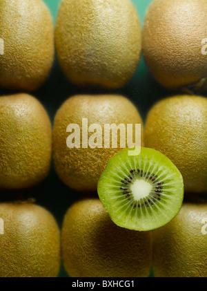 whole kiwi fruit with sliced half kiwi on green background - Stock Photo