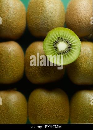whole kiwi fruit arranged in pattern with half kiwifruit slice - Stock Photo