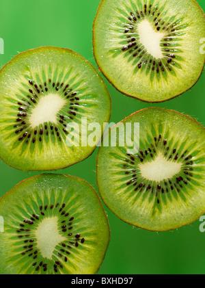 kiwi fruit slices on green background - Stock Photo