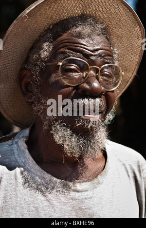 Old man with straw hat and glasses looking to the camera, Chinotimba, Zimbabwe, Africa. - Stock Photo
