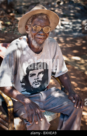 Old man with a Che Guevara T-Shirt, straw hat and glasses looking to the camera, Chinotimba, Zimbabwe, Africa. - Stock Photo