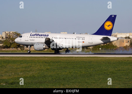 Lufthansa Airbus A319 airliner touching down on the runway while landing in Malta - Stock Photo