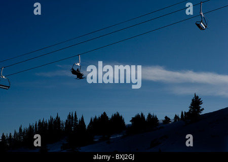 Ski chair lift, ascending mountain, in silhouette - Stock Photo
