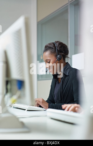 female african american customer service representative talking on the phone and typing on pc. Vertical shape, side - Stock Photo
