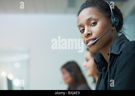 multiethnic group of female customer service representatives talking on the phone, with african woman looking at - Stock Photo