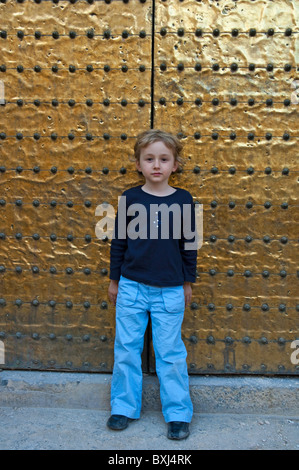 Little girl leaning against a bronze door belonging to the Cathedral de Cordoba, a former medieval mosque in Cordoba, - Stock Photo