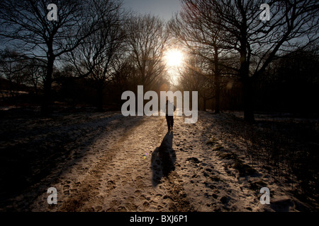 woman walks along a snow covered path in Rivington near Bolton - Stock Photo