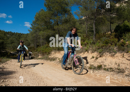 Father and son having fun riding their mountain bikes together on a dirt road, Vitrolles, Provence, France. - Stock Photo
