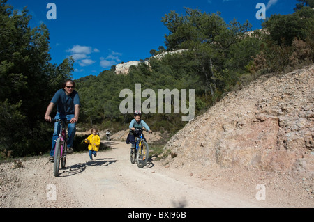 Father rides along dirt road on mountain bike with his son while his daughter runs alongside them, Vitrolles, Provence, - Stock Photo