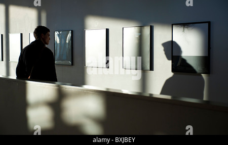 a man looking at photographs in an art gallery, Aberystwyth Arts Centre, Wales, UK - Stock Photo