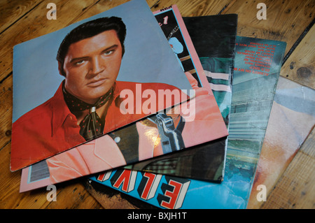 A selection of Elvis Presley records spread out on a wooden floor - Stock Photo