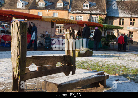Stocks in the foreground and farmer's market in background in the village  of Stow on the Wold in the Cotswolds. - Stock Photo