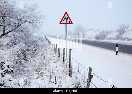 Winter road with freezing fog, snow and warning sign, near Floak on the road to Glasgow, Ayrshire, Scotland - Stock Photo