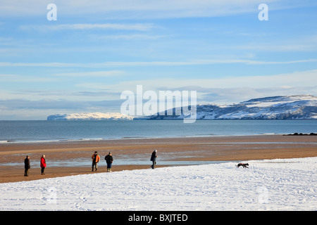 View to Great Orme across Red Wharf Bay (Traeth Coch) sea with people on snow covered beach in winter 2010. Benllech, - Stock Photo