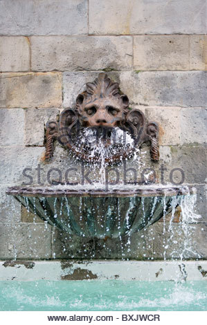 Antique fountain in a wall. Water is flowing from the mask - Stock Photo