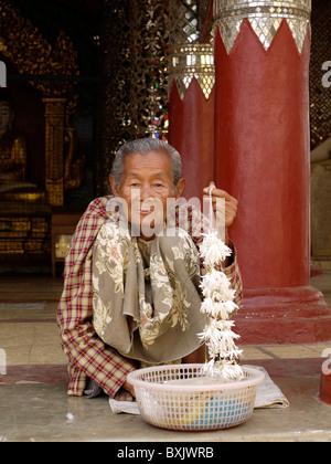 Woman selling flowers at Shwezigon Paya, Bagan, Burma, Myanmar - Stock Photo
