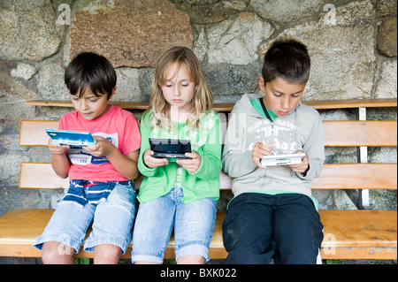 Children playing on Nintendo DS handheld games console, Spain - Stock Photo