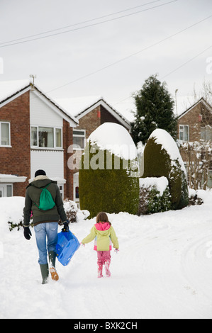 A father and daughter walking home in the snow after tobogganing / sledging - Stock Photo