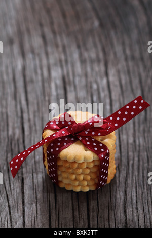 Cookies decorated with dark red polka dots ribbon on the wooden background - Stock Photo