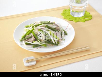 Stir fried pork and garlic stems - Stock Photo