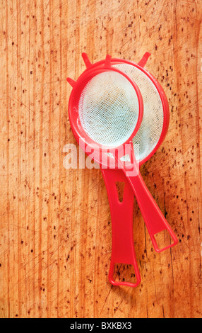 Two different sizes of red sifters on timber - Stock Photo