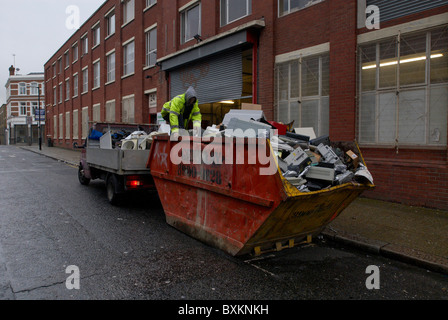 Scrap metal collectors searching through old office equipment in a skip South London UK - Stock Photo