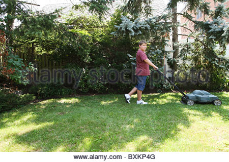 Boy mowing grass with lawnmower - Stock Photo