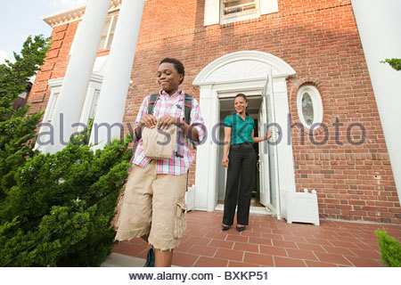 Mother sending son off with packed lunch in the morning - Stock Photo