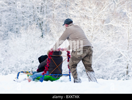 Dad pushes his child's sledge down the hill in Worcestershire, England, during the winter of 2010. - Stock Photo