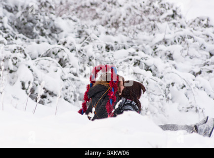 Teenage girls sledging down a hill in snow covered Redditch, Worcestershire, England - Stock Photo