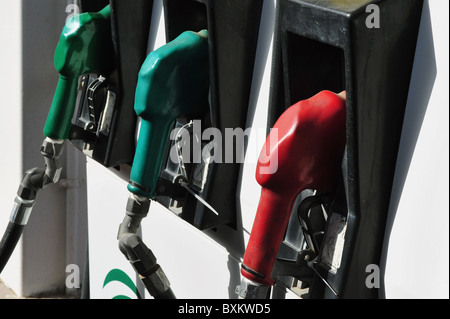 Car Fuel Consumption - Pump nozzles in gas station - Stock Photo