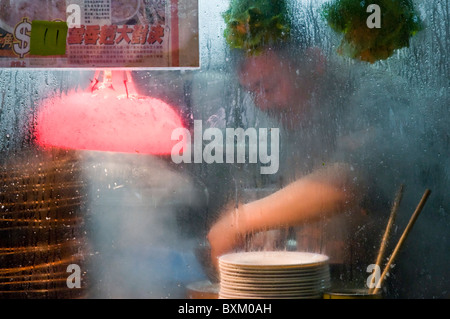 Asian man preparing food at outdoor stall on city street in downtown Hong Kong China - Stock Photo
