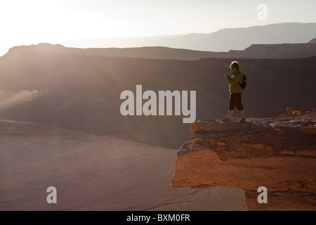 Lady stood on rock looking at sunset over Valley of the Moon, nr. San Pedro de Atacama, Chile, South America. - Stock Photo
