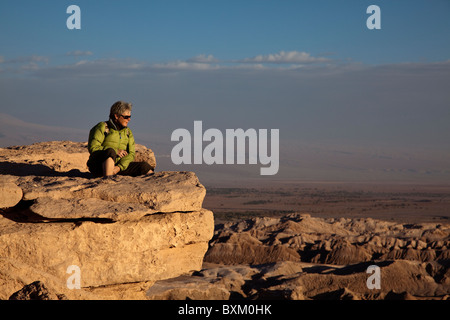 Lady sat on rock looking at sunset over Valley of the Moon, nr. San Pedro de Atacama, Chile, South America. - Stock Photo