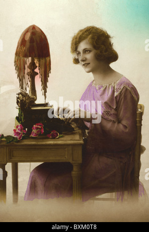 people, 1900 - 1930, young woman typing on typewriter, coloured photograph, Belgium, 1923, Additional-Rights-Clearences - Stock Photo