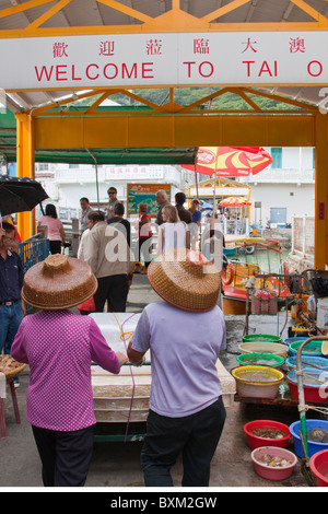 Tai O, Lantau Island, Hong Kong, China, Asia, ladies in Chinese hats push new mattress through village - Stock Photo