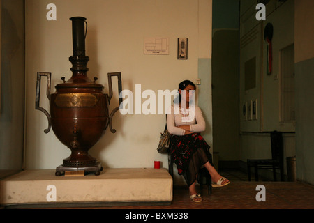 Custodian sits beside a huge Tula samovar in the museum of the Ark Fortress in Bukhara, Uzbekistan. - Stock Photo