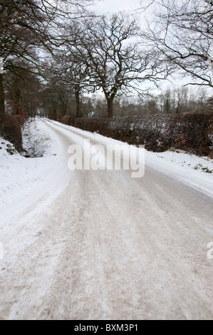 Untreated rural road covered in ice formed from frozen, compacted snow. Tyre (tire) tread marks are visible in the - Stock Photo
