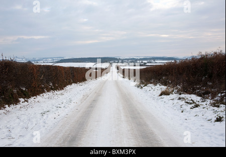 Untreated rural road covered in ice formed from frozen, compacted snow. - Stock Photo