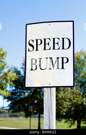 A white informational speed bump ahead sign in a local park in South Carolina, USA. - Stock Photo