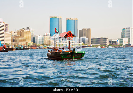 Traditional Arabian boat, abra or dhow moored in the Dubai Creek, Old Dubai, UAE, against a backdrop of modern buildings. - Stock Photo
