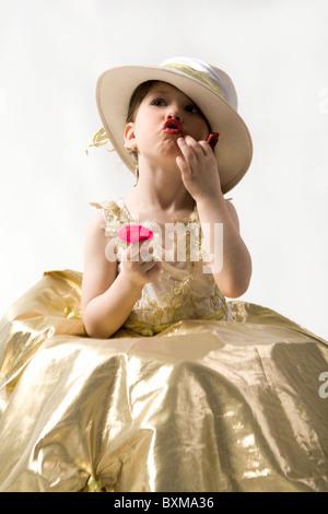 Isolated on white sweet brunette little girl in light goldish dress and white hat making up her lips - Stock Photo