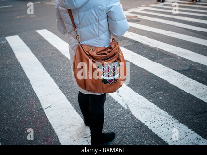 A woman with a leather Gucci handbag showing their 'Joy' Hearts and Roses design - Stock Photo