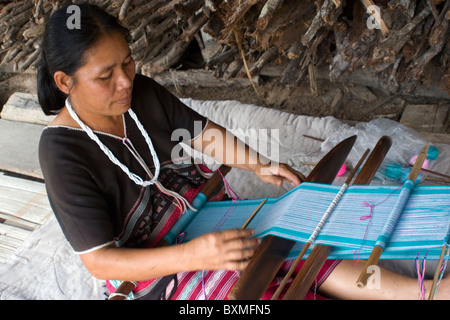 An ethnic Lahu woman is weaving colorful cloth by hand in Ban Mae Han village Thailand. - Stock Photo