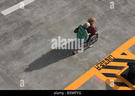 wife pushing her disabled husband in a wheel chair on an accessible tour  showing the affection of senior couples - Stock Photo